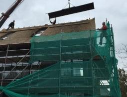 Nokkappen hijsen op een rieten dak 12 meter hoog 12 meter vlucht 400 kg
